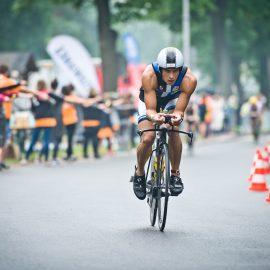 Zdjęcie z Triathlon Sieraków, rywalizacja rowerzystów w pobliżu mety. W tle kibice