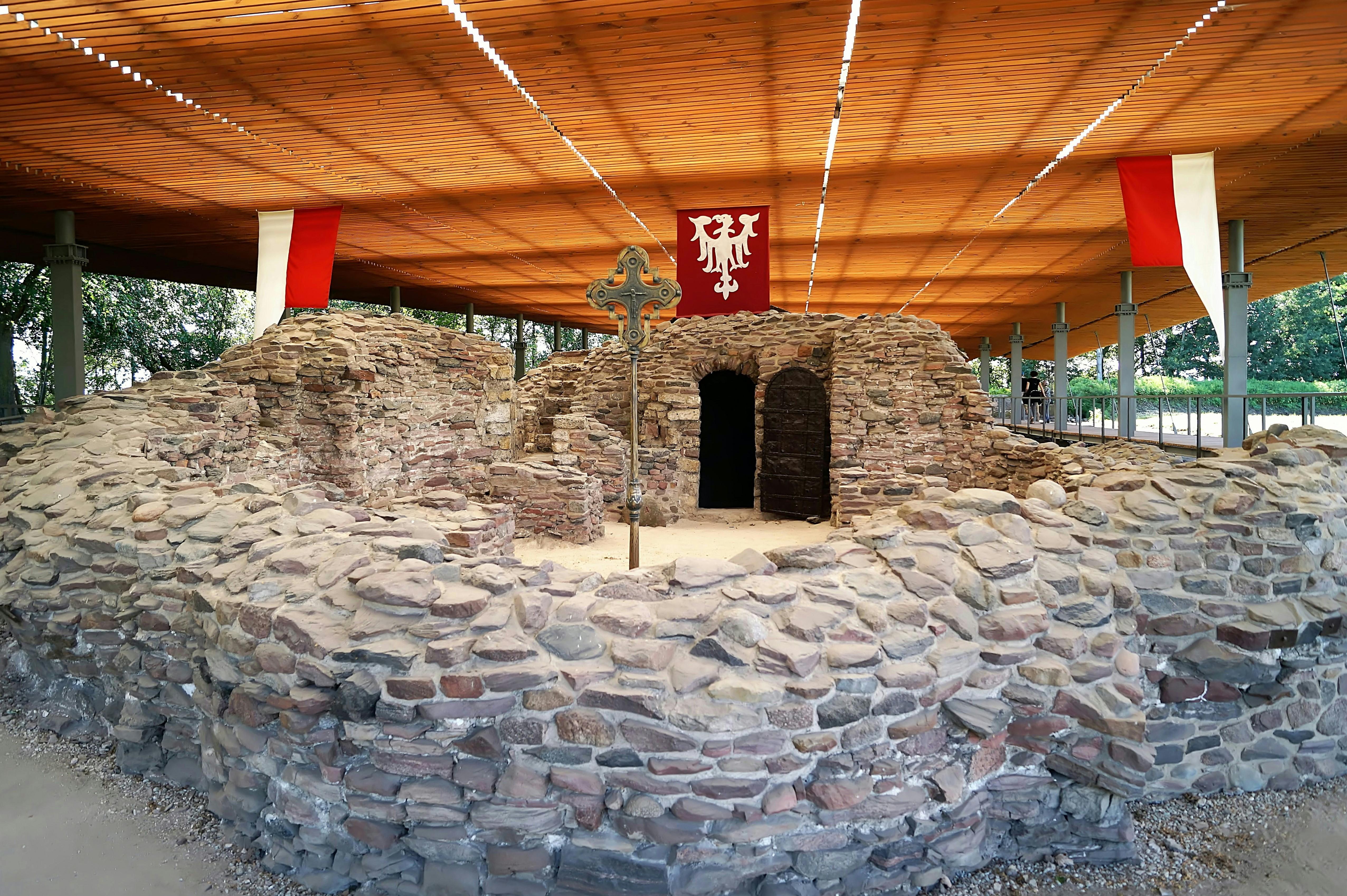 Ruiny wczesnośredniowiecznego palatium na Ostrowie Lednickim. Kamienne fundamenty nakryte ochronnym dachem.